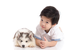 Cute asian boy and siberian husky puppy lying Royalty Free Stock Photos