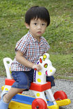 Cute Asian boy on a toy horse Royalty Free Stock Image
