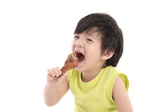 Cute asian boyeating roasted chicken Royalty Free Stock Photos