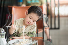Cute Asian chid eating Spaghetti Carbonara Stock Photography