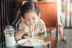 Cute Asian chid eating Spaghetti Carbonara Royalty Free Stock Photos