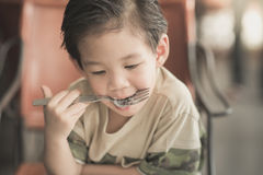 Cute Asian chid eating Spaghetti Carbonara Royalty Free Stock Images