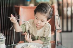 Cute Asian chid eating spaghetti carbonara. In restaurant, vintage fiter Royalty Free Stock Photo