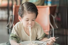 Cute Asian chid eating spaghetti carbonara. In restaurant, vintage fiter Stock Images