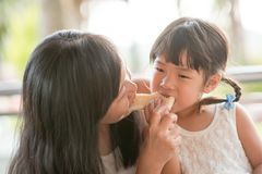 Mom and child sharing bread stock photo