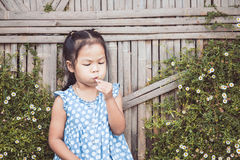 Cute asian child girl blowing little flower in the garden stock photos