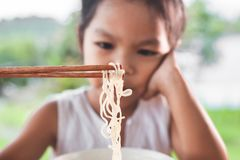 Cute asian child girl bored to eat Instant noodles. For her meal stock image
