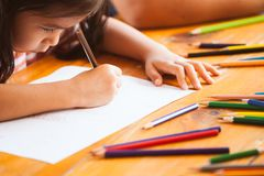 Cute asian child girl drawing and painting with crayon. With fun stock images