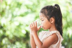 Cute asian child girl drinking fresh water from glass stock image