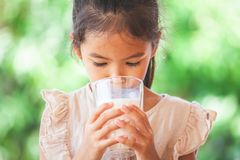 Cute asian child girl is drinking a milk from glass. On green nature background stock photography