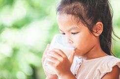 Cute asian child girl is drinking a milk from glass stock images