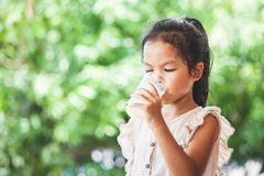 Cute asian child girl is drinking a milk from glass. On green nature background royalty free stock image