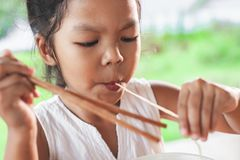 Cute asian child girl eating delicious instant noodles. With chopstick in the nature background stock photography
