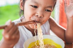 Cute asian child girl eating delicious instant noodles Royalty Free Stock Photo