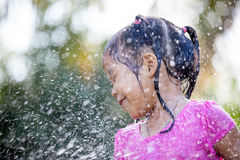 Cute asian child girl having fun to bath and playing water. Splash in outside Royalty Free Stock Image