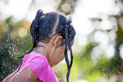Cute asian child girl having fun to bath and playing water. Splash in outside Stock Photos