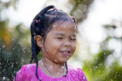 Cute asian child girl having fun to bath and playing water. Splash in outside Stock Images