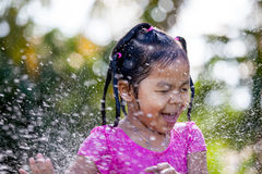 Cute asian child girl having fun to bath and playing water. Splash in outside Stock Image