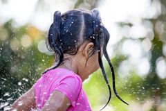 Cute asian child girl having fun to bath and playing water. Splash in outside Stock Photography
