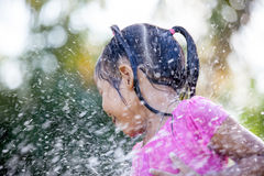 Cute asian child girl having fun to bath and playing water. Splash in outside Royalty Free Stock Photo