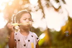 Cute asian child girl having fun to blow soap bubbles in outdoor. At sunset Royalty Free Stock Images