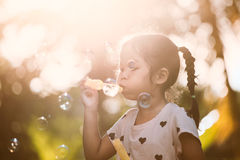 Cute asian child girl having fun to blow soap bubbles in outdoor. At sunset Stock Photo