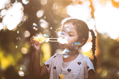 Cute asian child girl having fun to blow soap bubbles in outdoor. At sunset Stock Photography