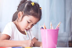 Cute asian child girl having fun to draw and paint with crayon Royalty Free Stock Images