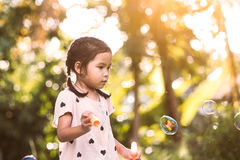 Cute asian child girl having fun to play with bubbles in outdoor Royalty Free Stock Photos