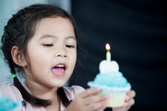 Cute asian child girl having fun to sing a song and blowing. Birthday cupcake in party Royalty Free Stock Images