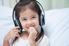 Cute asian child girl in headphones listening the music royalty free stock image
