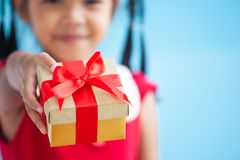 Cute asian child girl holding beautiful gift in hand stock images