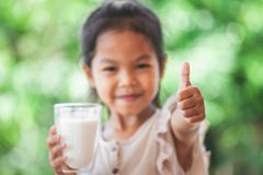 Cute asian child girl holding glass of milk and make strong gesture stock photography