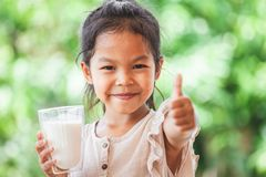 Cute asian child girl holding glass of milk and make strong gesture stock photos