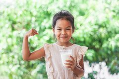 Cute asian child girl holding glass of milk and make strong gesture royalty free stock image