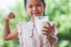 Cute asian child girl holding glass of milk and make strong gesture royalty free stock photography