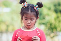 Cute asian child girl opening and looking money in red envelope. And wishing you a happy in Chinese New Year Royalty Free Stock Image
