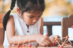 Cute asian child girl playing and creating with play dough. And toothpick. Child concentrated with play dough building a molecule model royalty free stock images