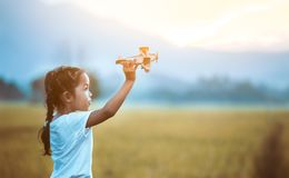 Cute asian child girl playing with toy wooden airplane royalty free stock images
