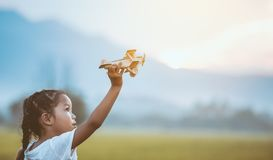 Cute asian child girl playing with toy wooden airplane royalty free stock photo