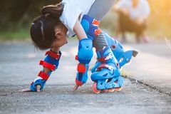 Asian child girl riding on roller skates and fall down in the park