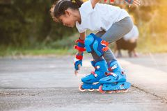 Asian child girl riding on roller skates in the park with fun