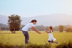 Cute asian child girl running to her mother to give a hug stock photography