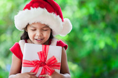 Cute asian child girl in santa red hat holding Christmas gift Royalty Free Stock Images