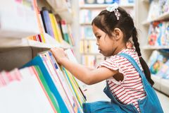 Cute asian child girl select book on bookshelf in bookstore royalty free stock image