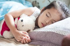 Cute asian child girl sleeping and hugging her teddy bear. In the bed Stock Photos
