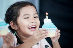 Cute asian child girl smiling and blow her birthday cupcake. Cute asian child girl smiling and having fun to blow her birthday cupcake in party Royalty Free Stock Photos