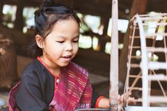 Cute asian child girl using traditional wooden spinning wheel. Cute asian child girl in Thai traditional dress using traditional wooden spinning wheel with fun Royalty Free Stock Photo