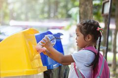 Cute asian child girl throwing plastic glass in recycling trash royalty free stock photo