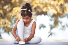 Cute asian child girl tying on feet pointe shoes Royalty Free Stock Image